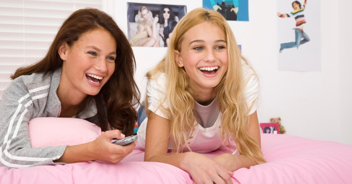 two girls lying on a pink bed laughing