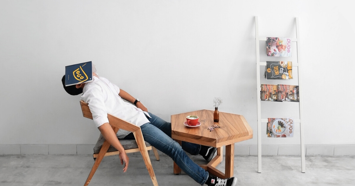 man slumped back in chair with book over his face