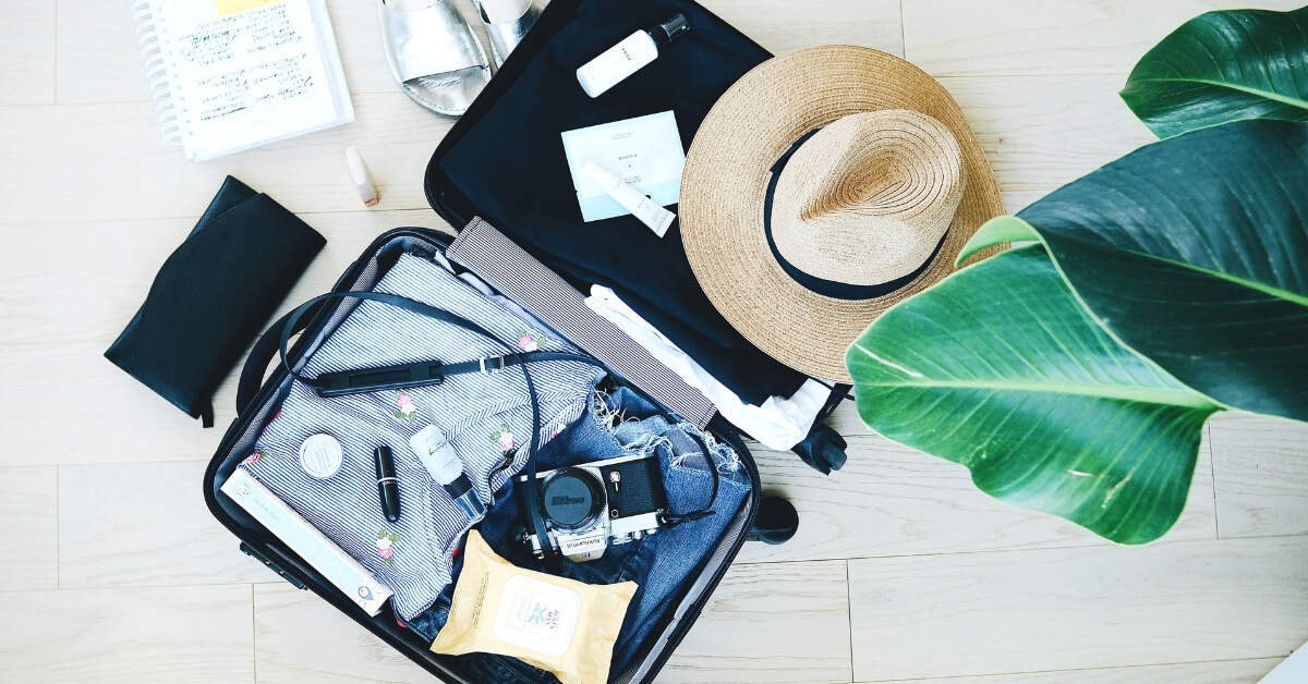 flatlay of open suitcase containing travel items beautifully laid out