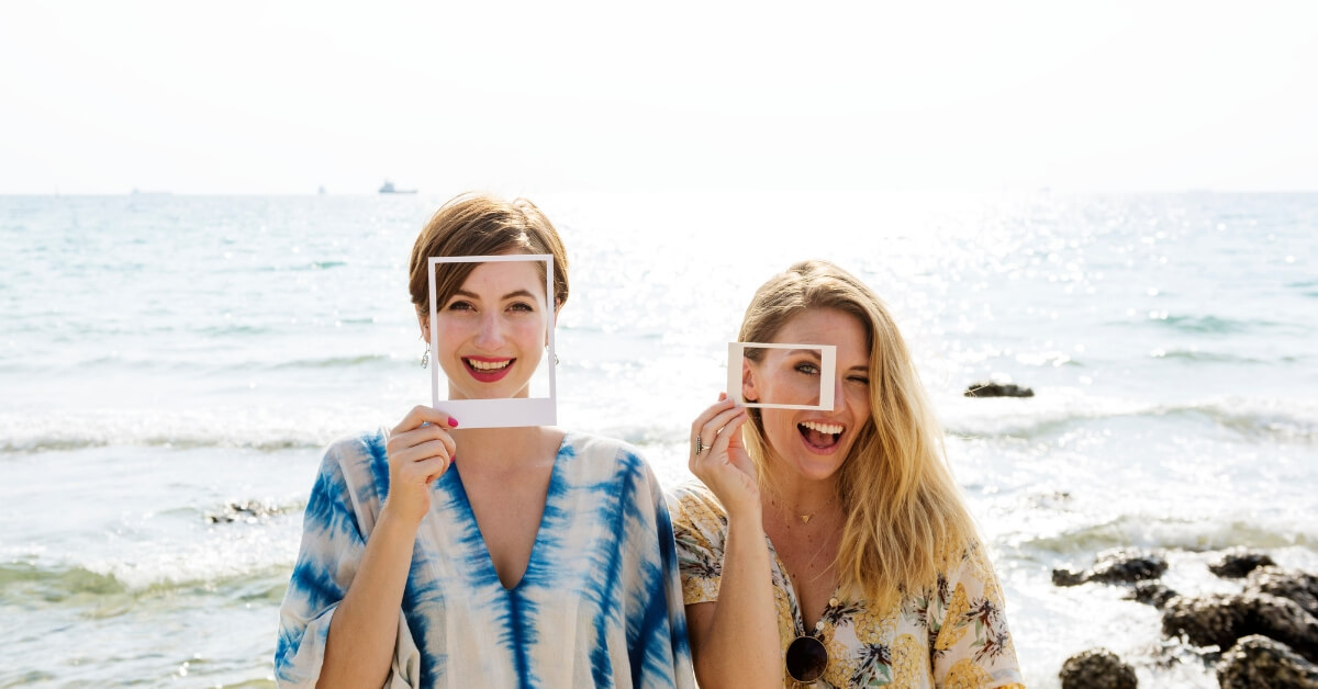 two women standing in from of ocean holding up Polaroid frames to their faces