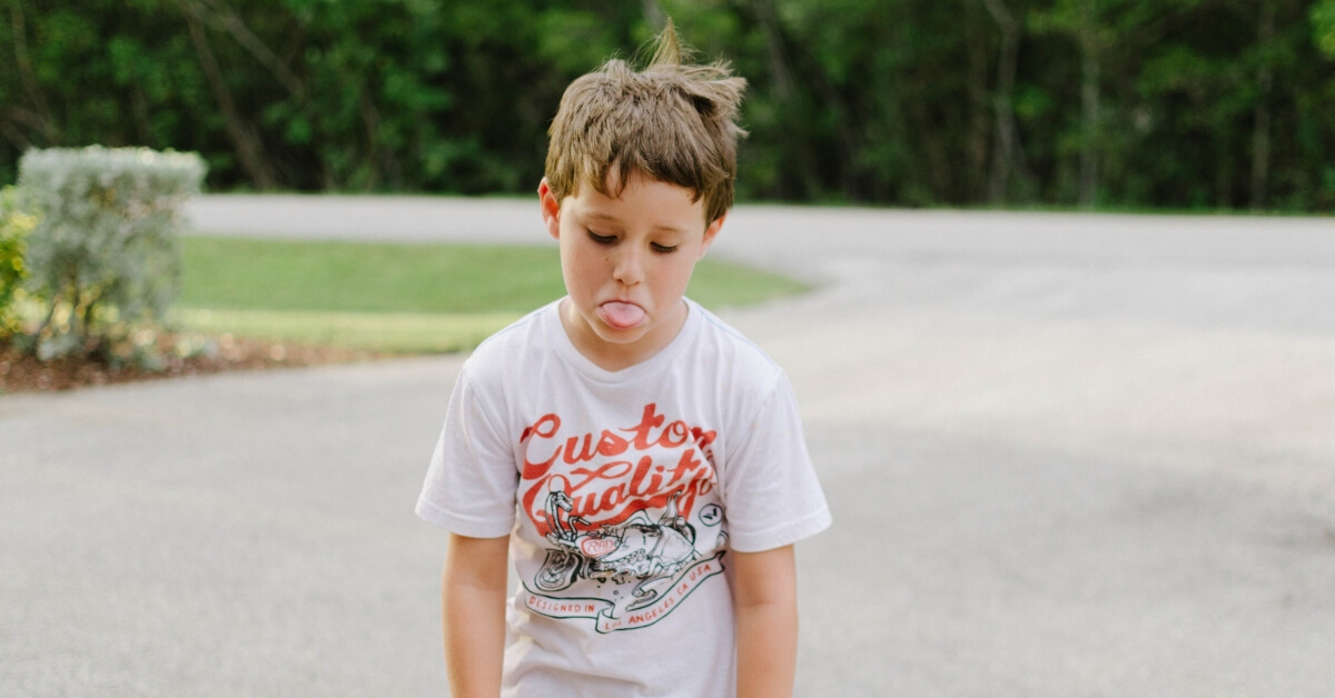 boy with slumped shoulders poking his tongue out