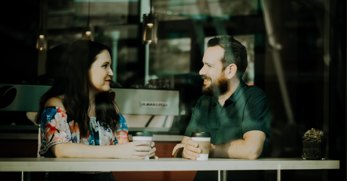 a man and woman talking over coffee