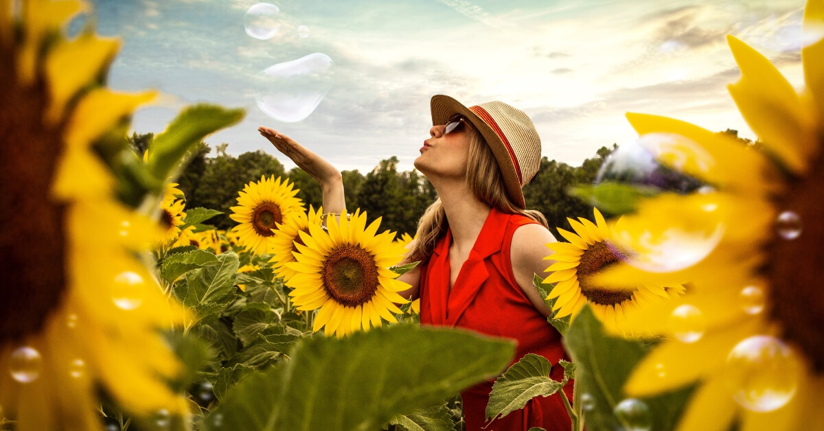 a woman blowing bubbles in a sunflower field