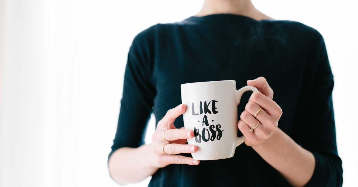 "woman holding a mug which says ""like a boss"" on it"