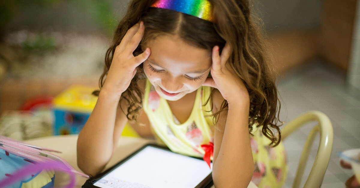 young girl smiling down at an iPad