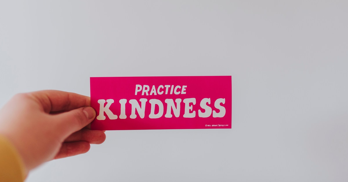 Hand holding a card that says Practice Kindness