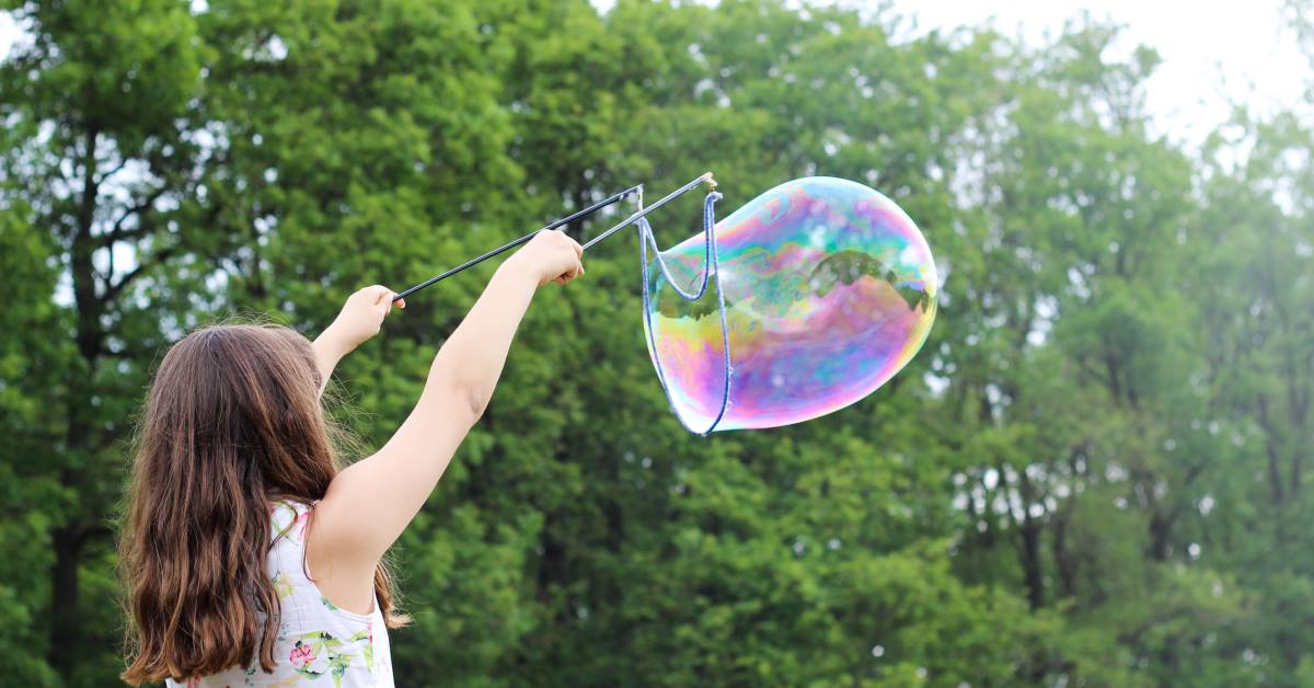 Young Girl playing using string and pole to create huge blown bubble