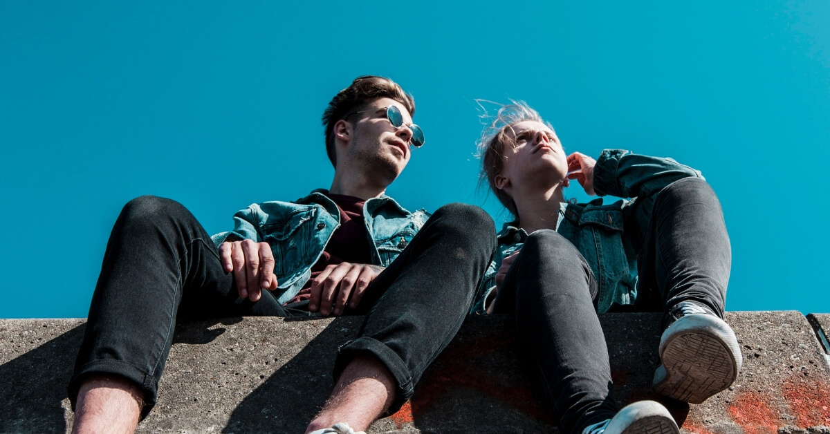 low angle looking up at two young people sitting on a brick wall