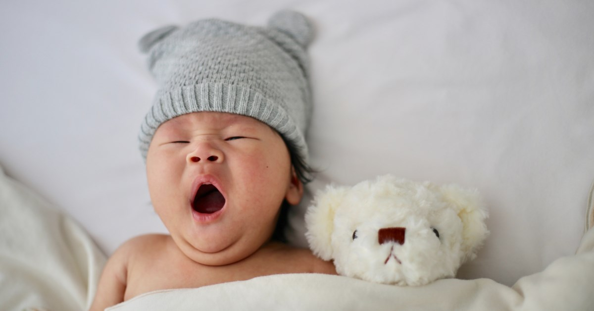 Baby with grey beanie yawning in bed next to teddy bear