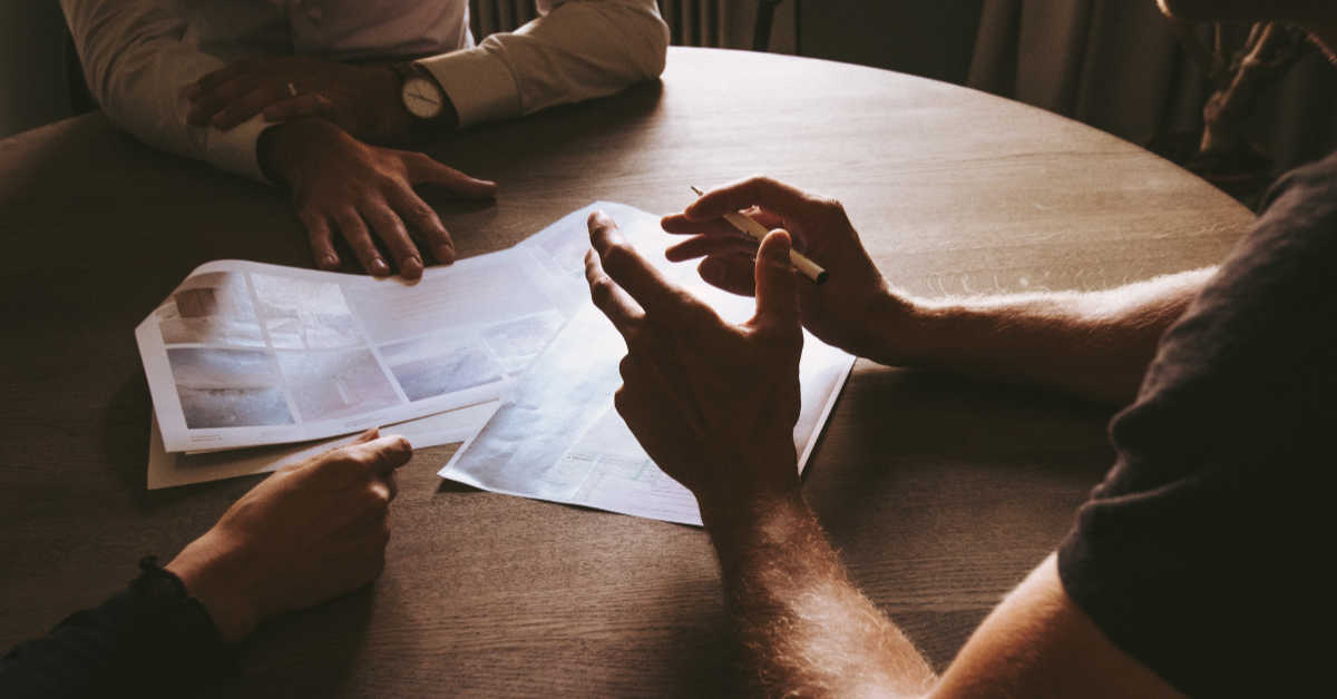 People sitting at table discussing plans on paper
