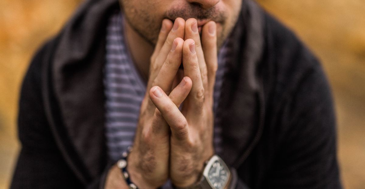 Man with hands together in front of his face looking thoughtful