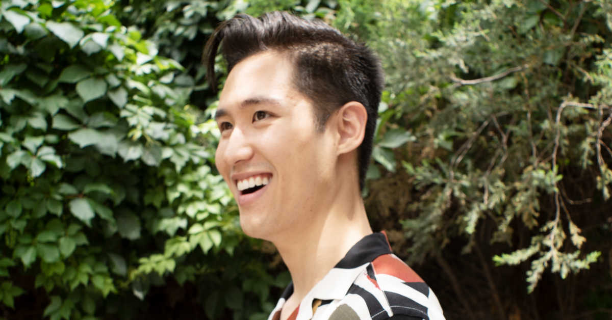 Brian Liu smiling standing in front of green hedge