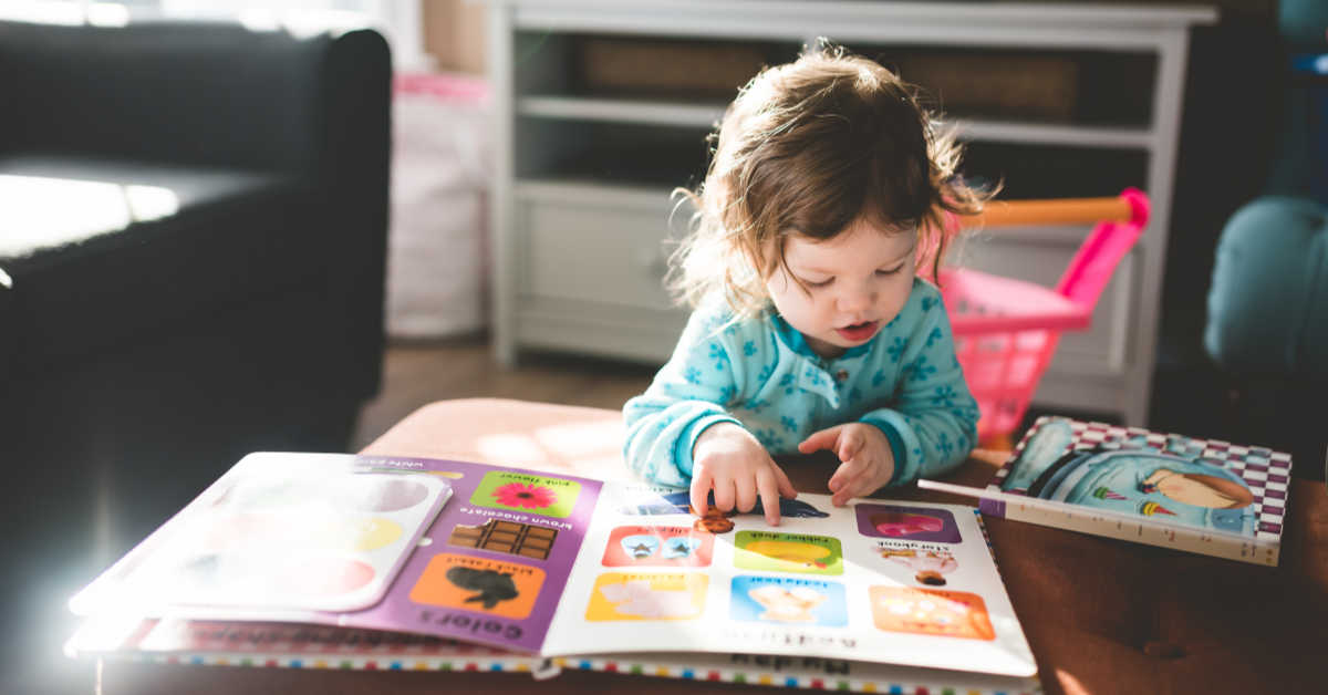 Little girl leaning over alphabet book