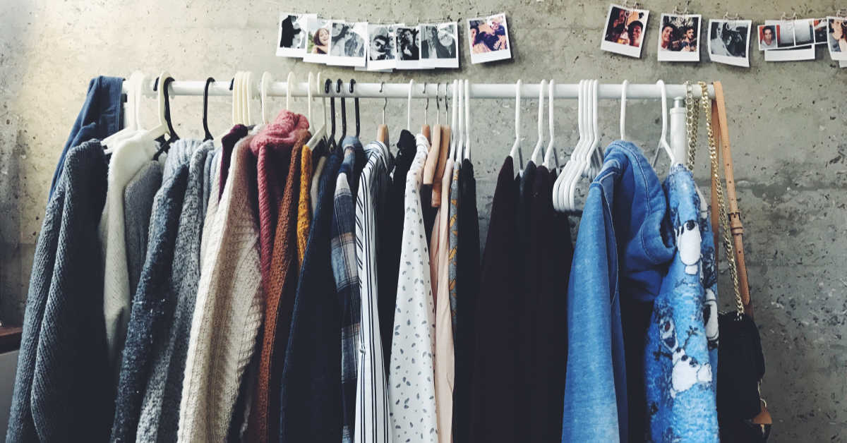 A rack of various sweaters and jumper hanging on coat hangers against a wall