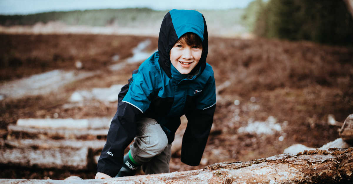 Boy climbing over log