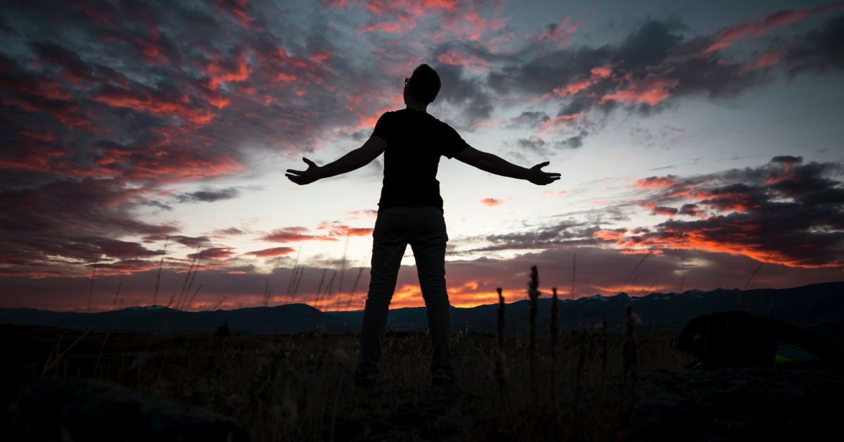 Person lifting their hands to the sky at sunset