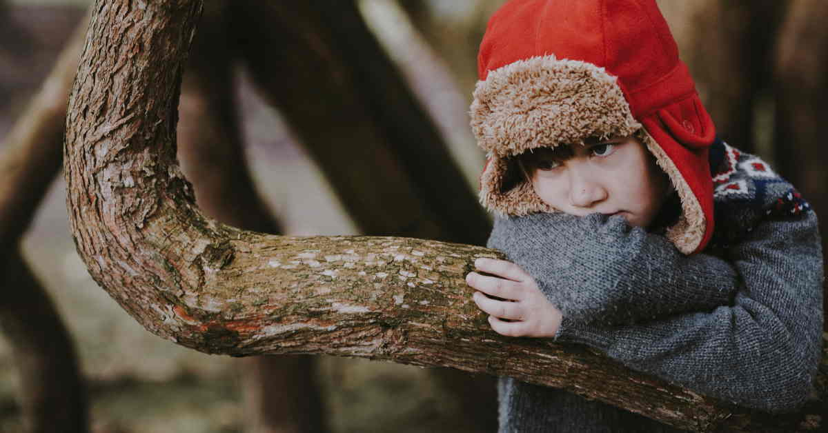boy hugging tree branch with bored look