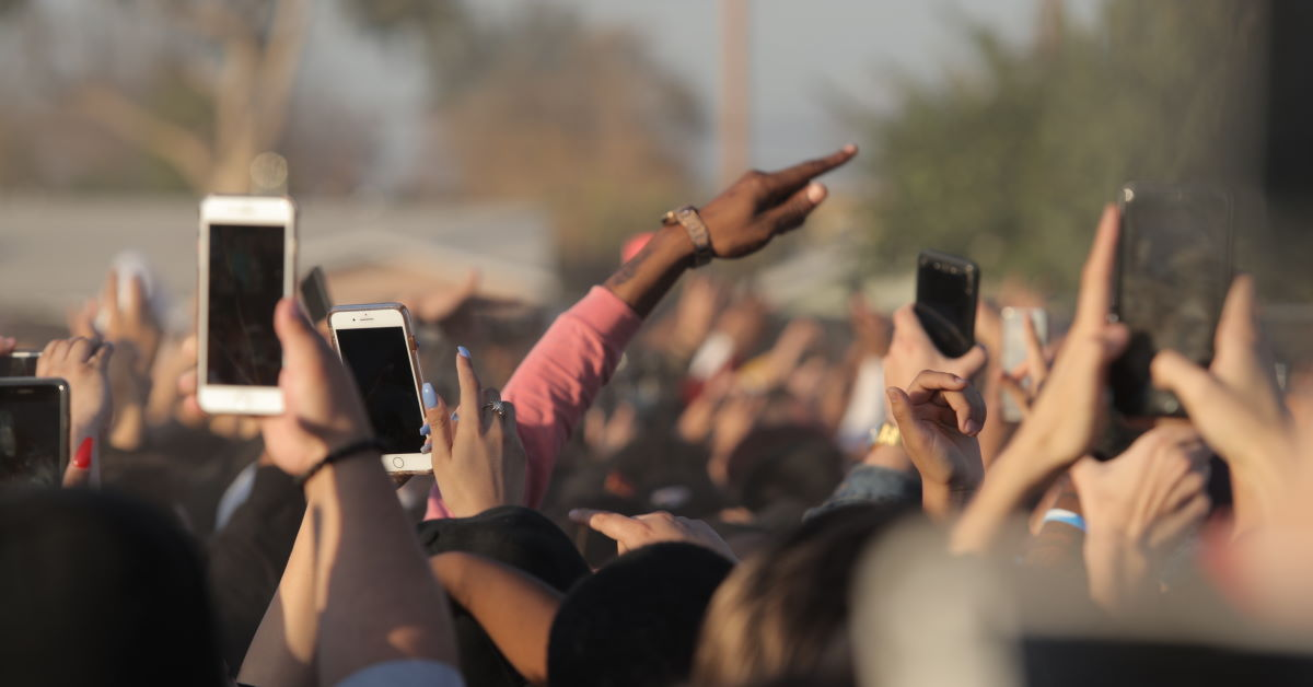 hands lifted in a crowd with smartphones