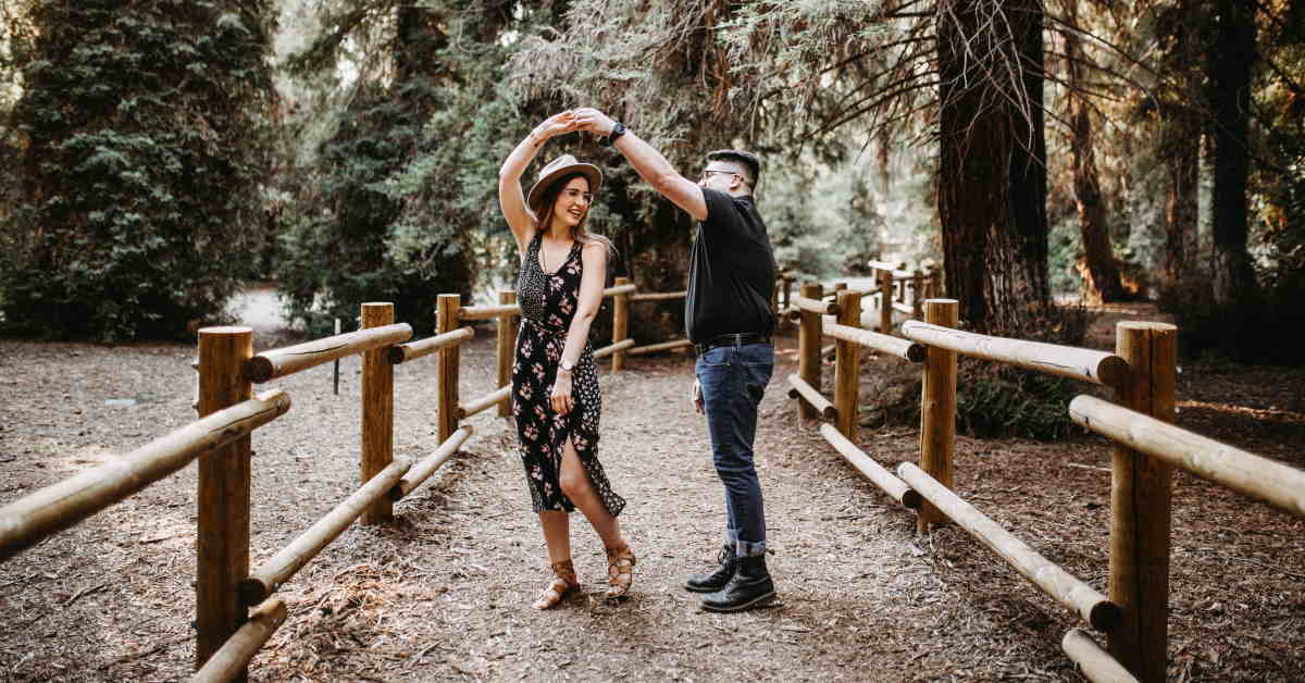 couple dancing on pathway in the woods
