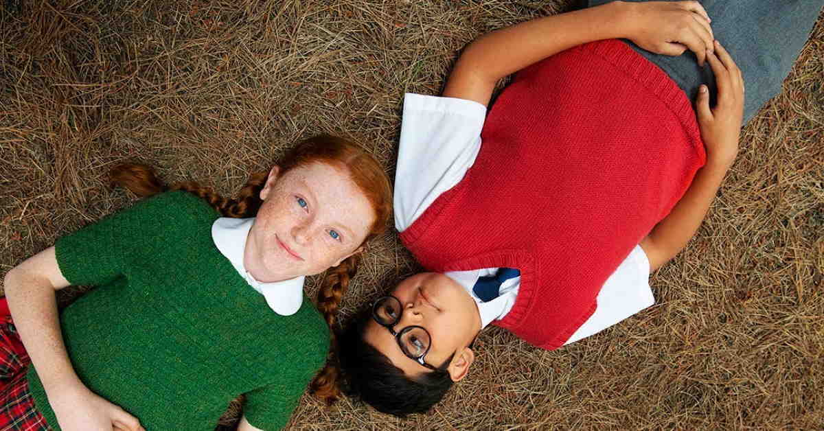 characters from the movie lying on the grass looking up at camera
