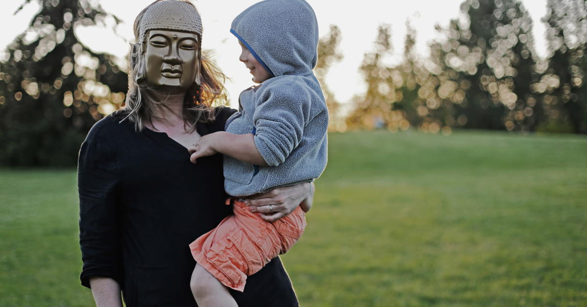 parent with mask carrying toddler with hoodie on grass field