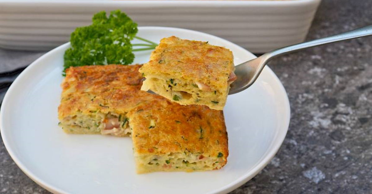 squares of zucchini slice on a plate with one picked up by a fork