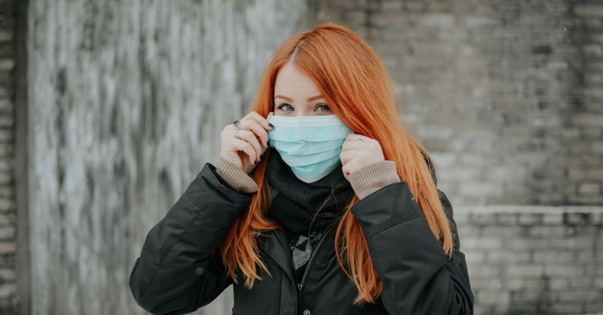 Woman with red hair putting on medical face mask