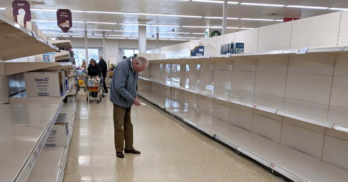 elderly man in a supermarket aisle with empty shelves