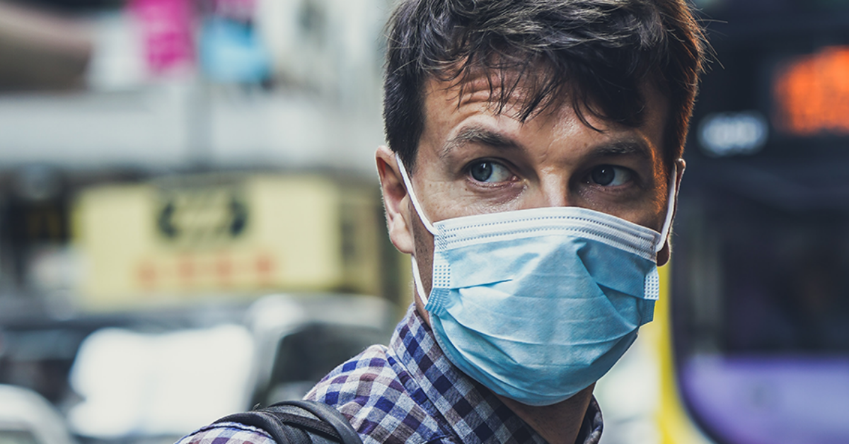 close up of man in a flu mask with blurred out street behind him