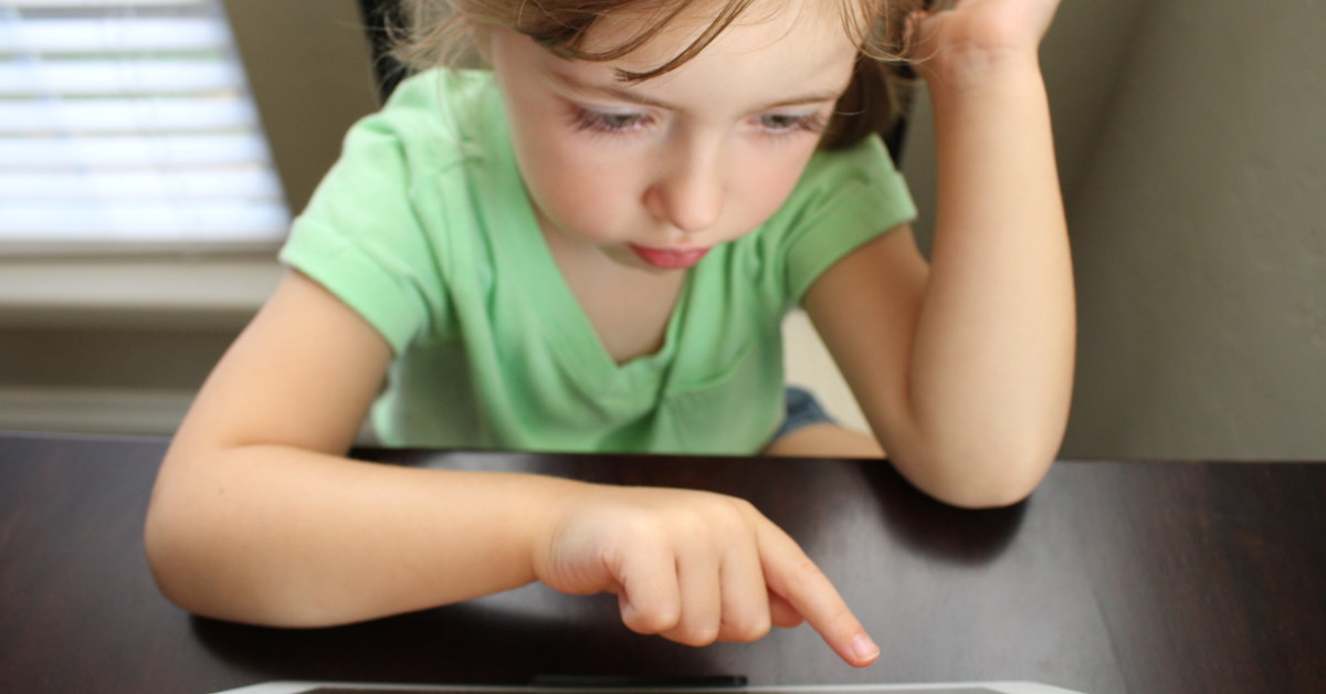 child searching ipad screen for information