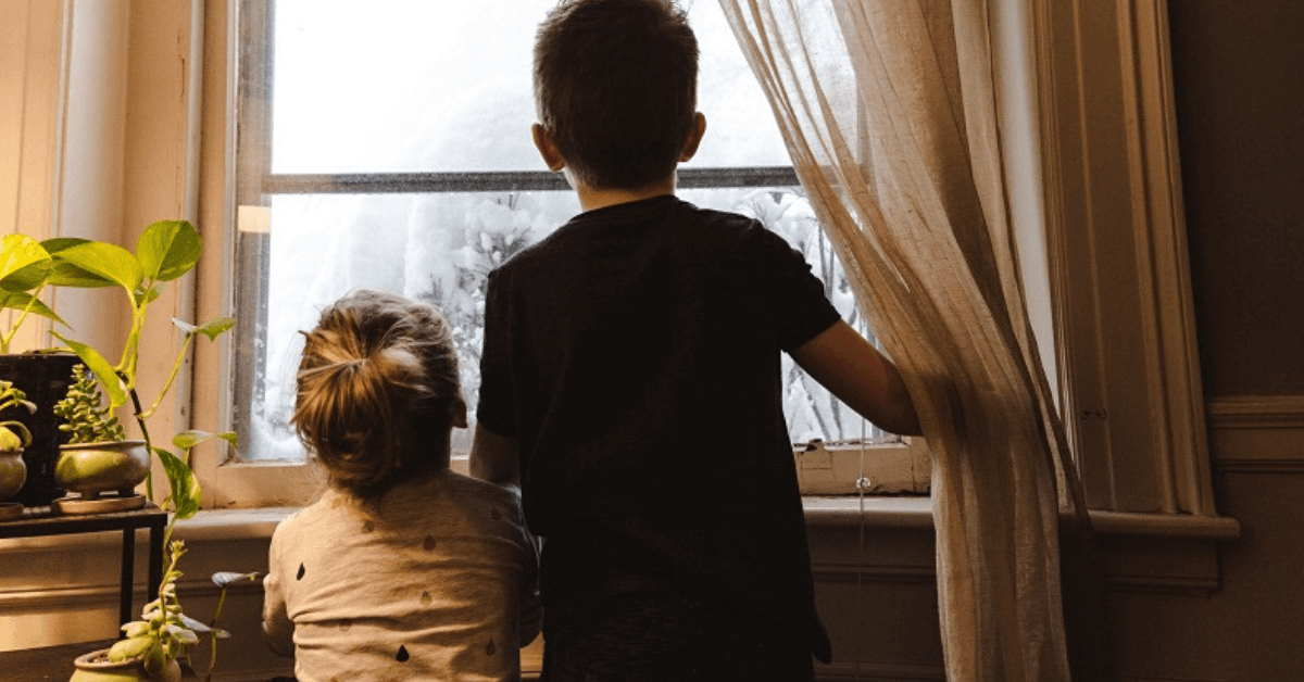 2 kids looking out a window