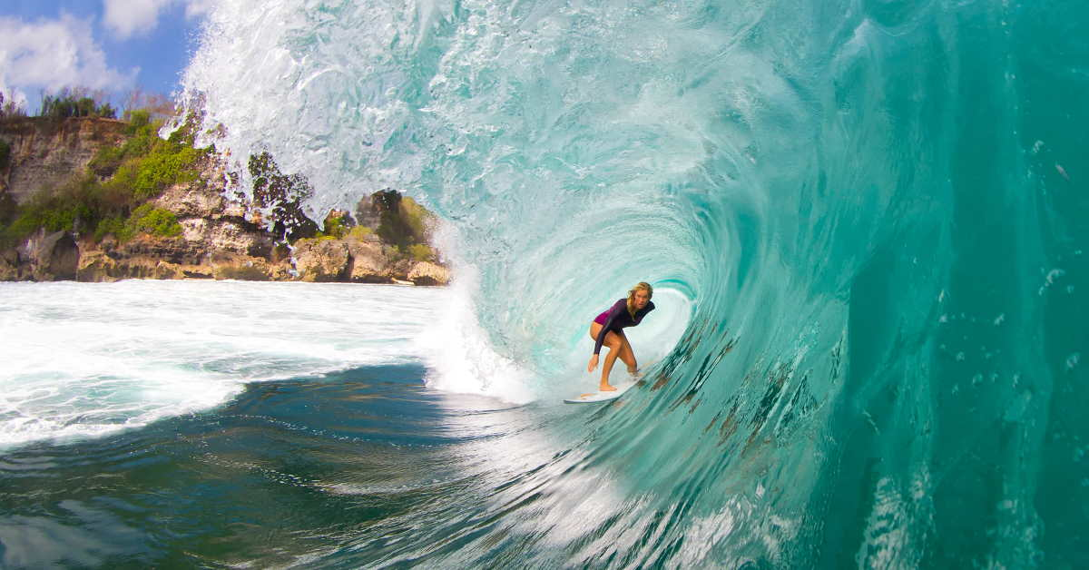 bethany hamilton riding a surfboard inside the curve of a wave