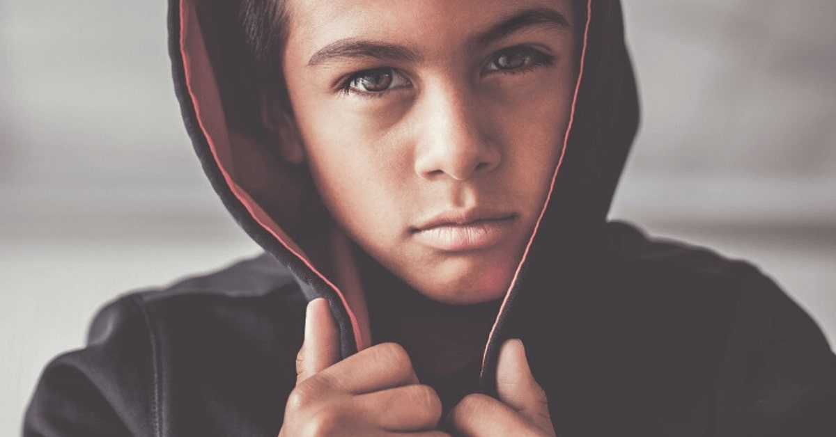 close up of a boy gripping the hood of his jacket