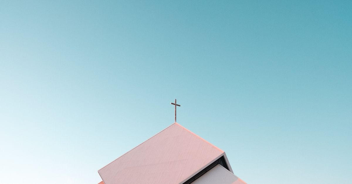 a photo of a cross on top of the roof of a church