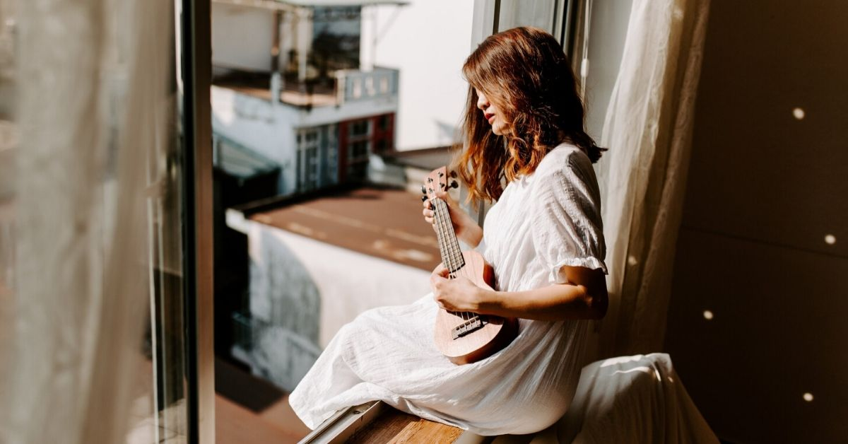 photo of woman playing ukelele sitting on a window frame