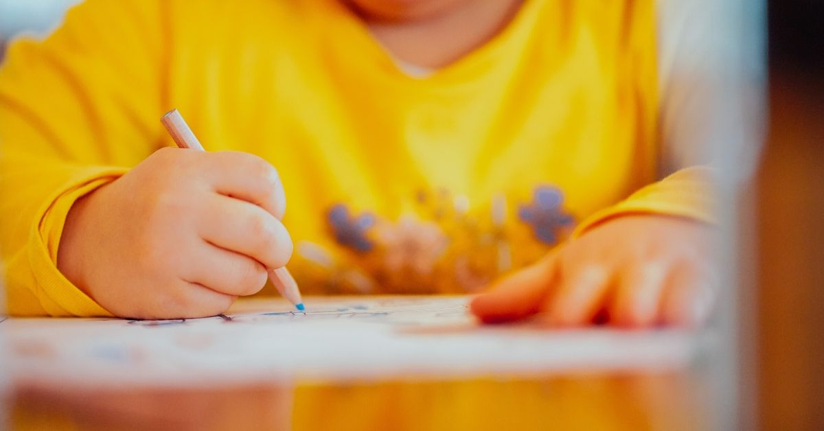 photo of a child in a yellow top drawing on paper