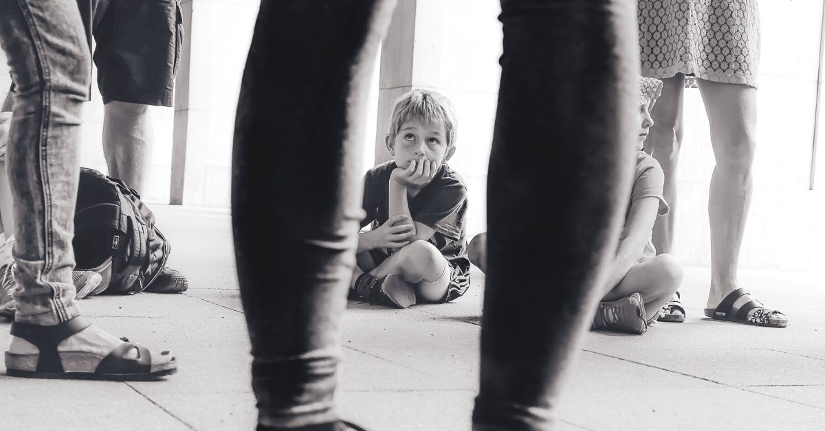 young boy sitting on floor looking up at someone
