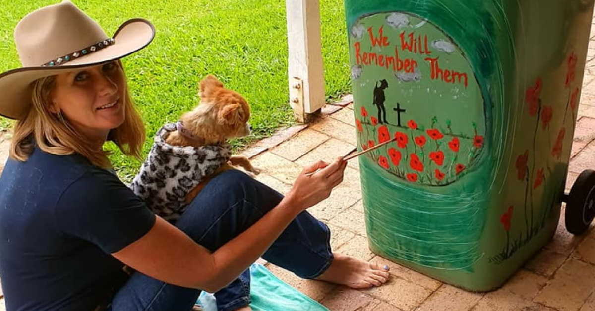Woman in cowboy hat with dog on lap paints Anzac Memorial picture on her wheelie bin