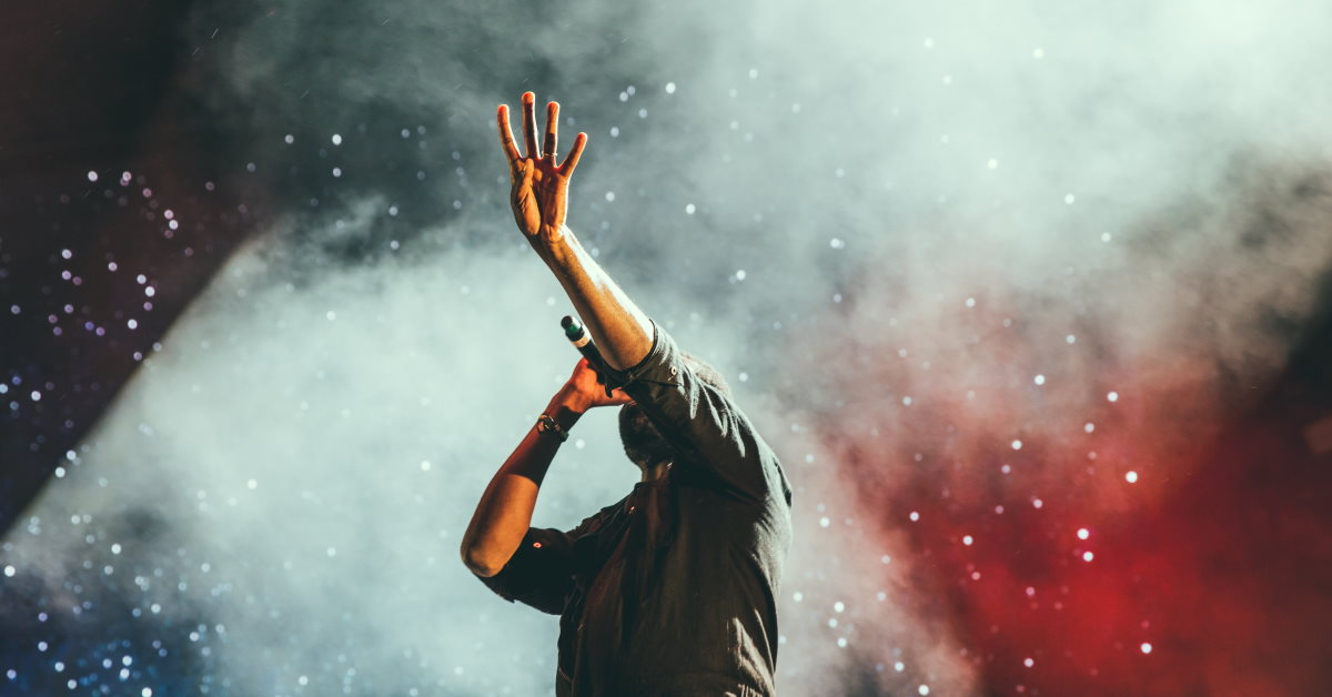 guy singing from stage reaching out in worship
