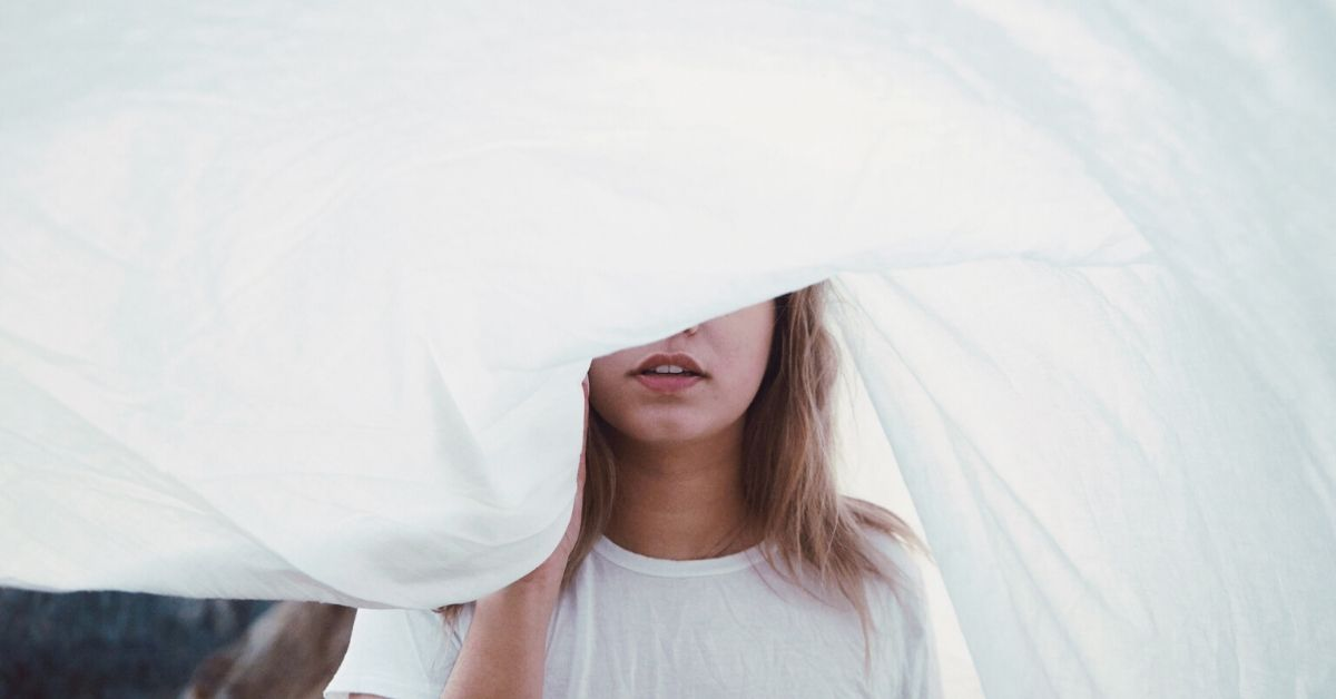 photo of a woman in white shirt with her face half shrouded by a big piece of cloth