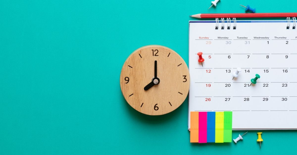 photo of a calendar, clock and sticky notes on a green background