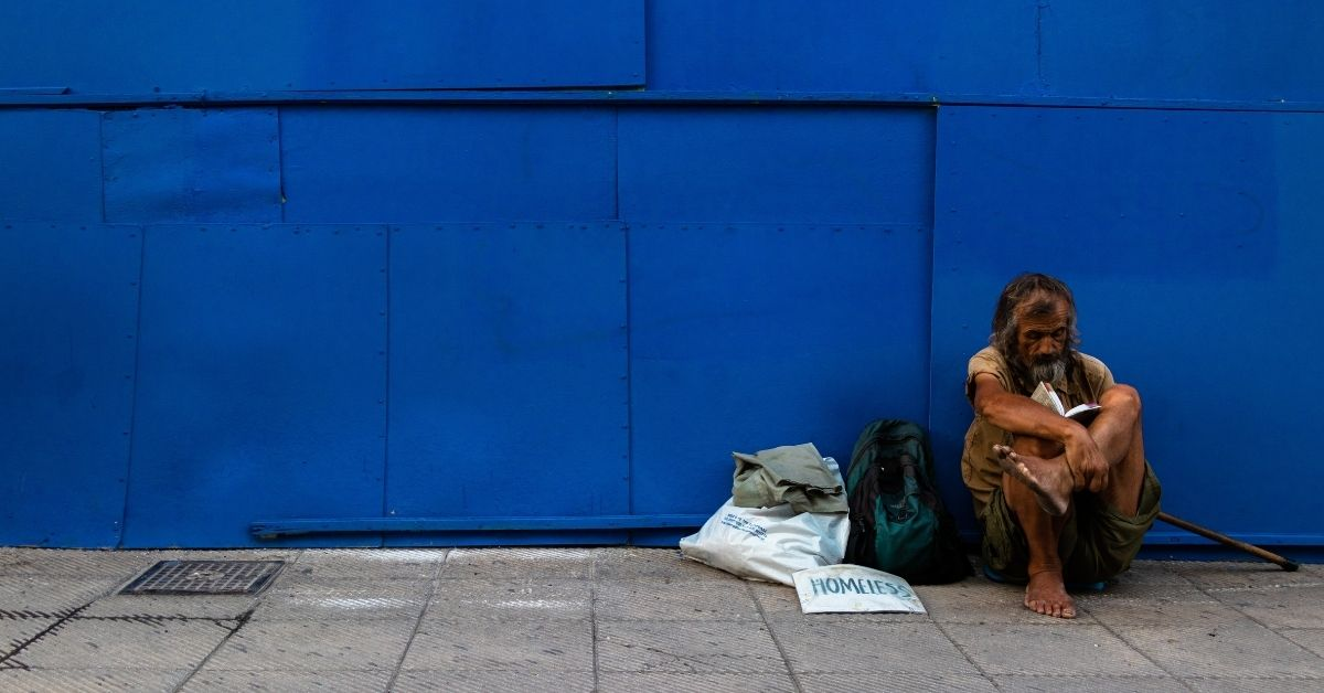 dishevelled homeless man sitting against a blue wall