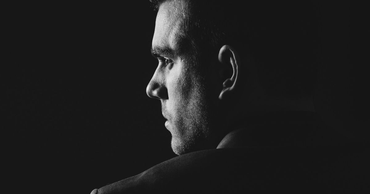 image of a black and white image of a shadowy profile of a man's face