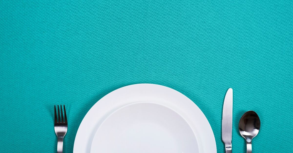 plate and cutlery on teal background