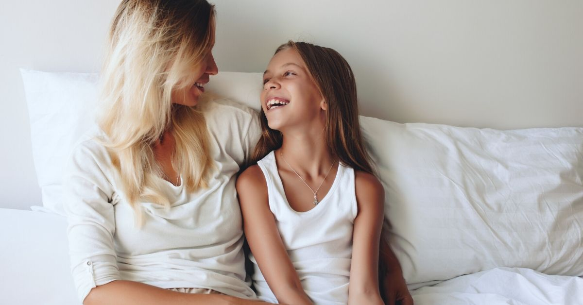 photo of a mother and daighter sitting up against pillows at home laughing and talking