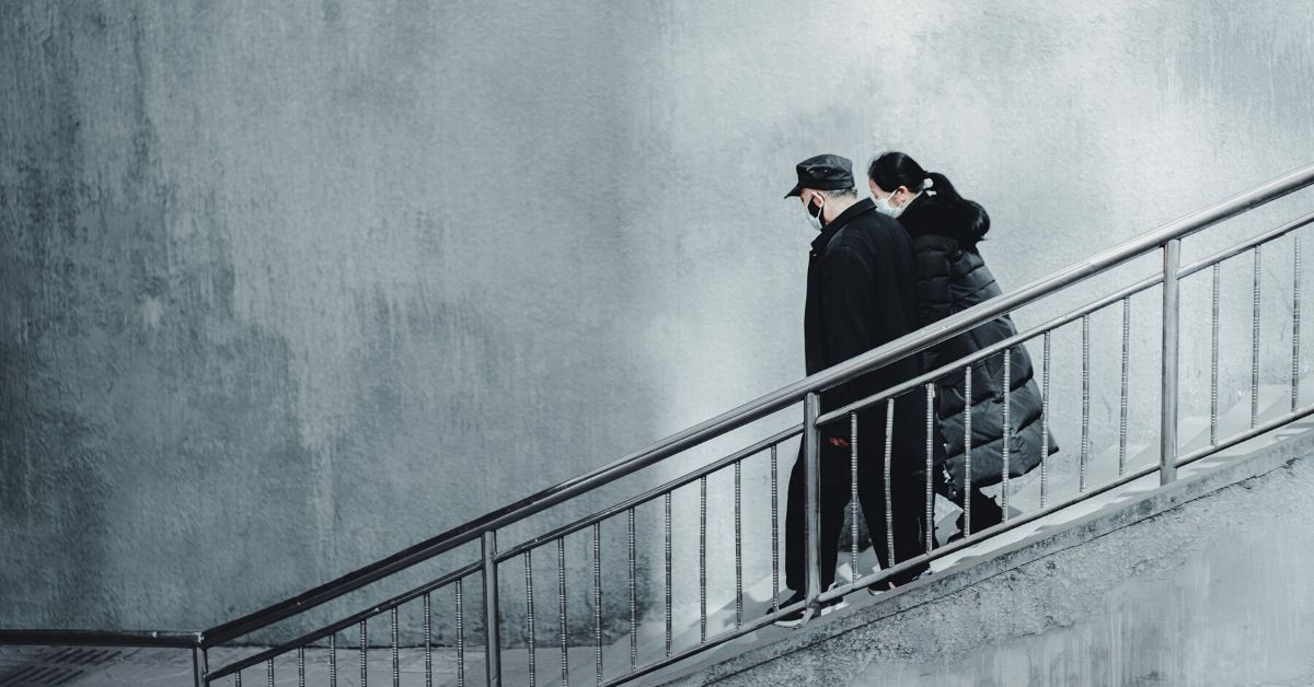 a photo of a man and a woman wearing masks due to the COVID-19 pandemic walking down stone stairs