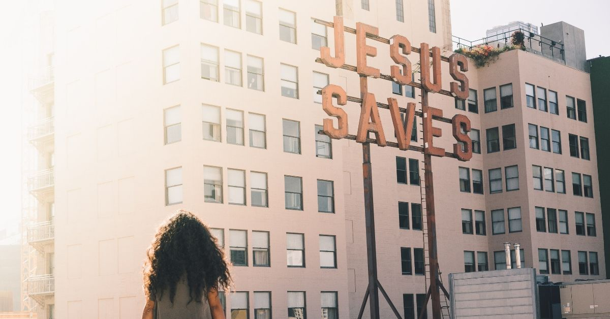 "photo of a woman sitting on a wall overlooking skyrises beside a sign which says ""jesus saves"""