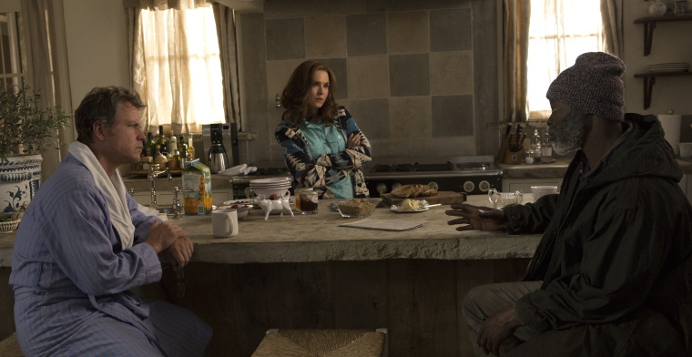 A film still of Ron, Debbie and Denver talking around a table