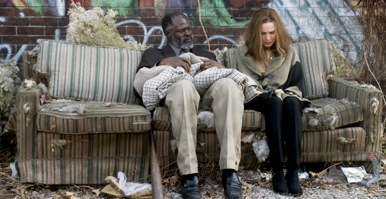 A film still of Denver and Debbie sitting on a dirty couch on the street surrounded by trash
