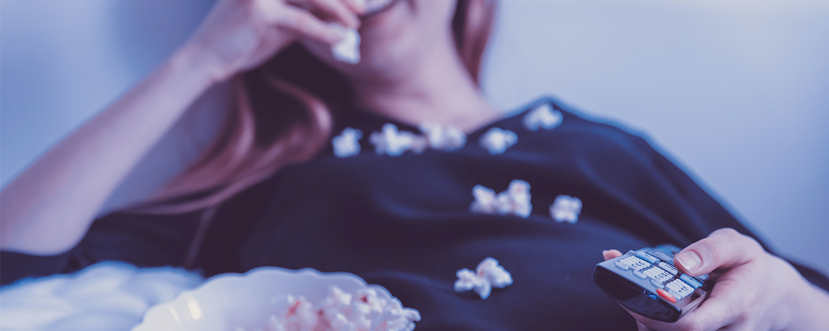 image of a woman lying back eating popcorn